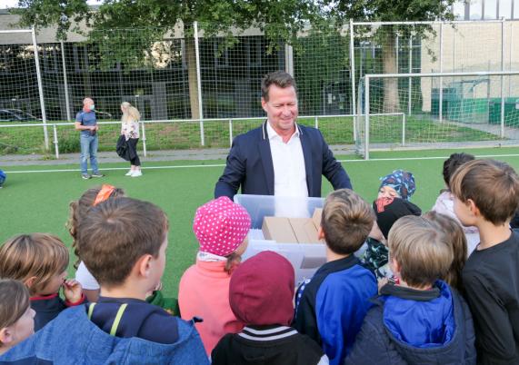 Bürgermeister Steffen Apelt übergibt Geschenke zur Einschulung.